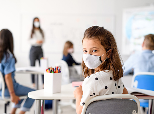 teacher instructs students in classroom wearing masks