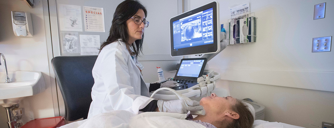 imaging technician performing a neck ultrasound on a patient in an exam room